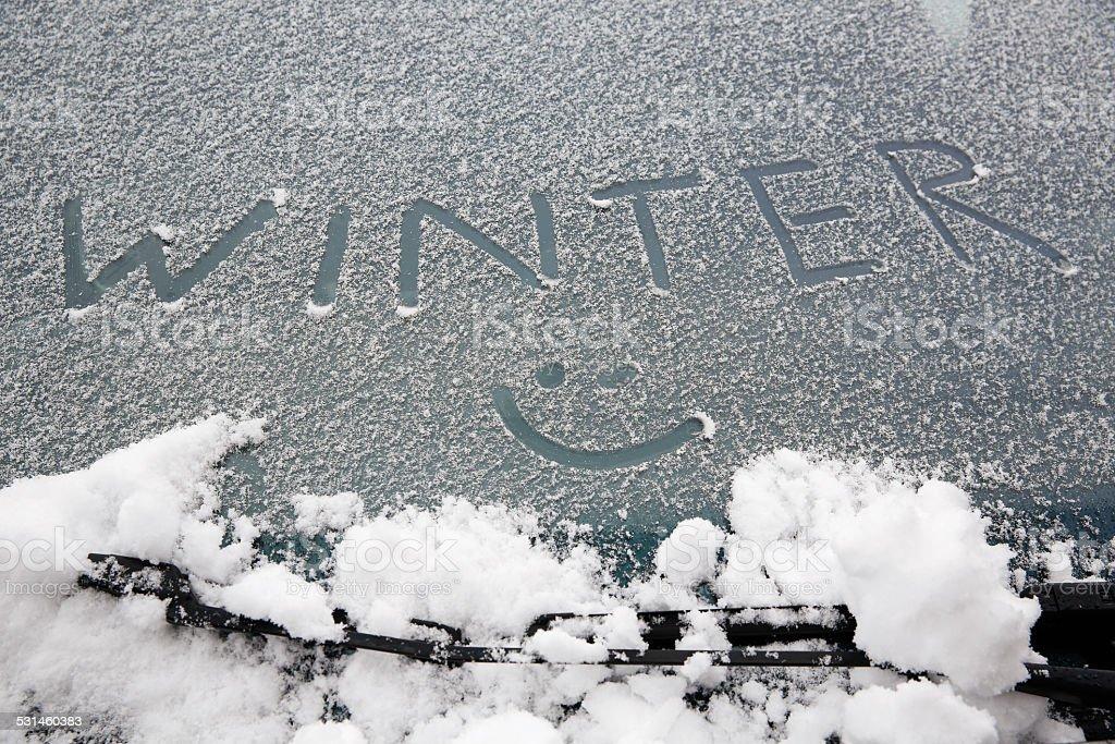 Smiley drawn on snowy windshield stock photo