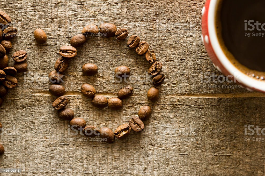 Smiley face made of coffee seeds on wooden plank stock photo