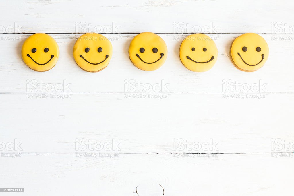 Smiley faces on wooden white background. Top view, flat lay stock photo