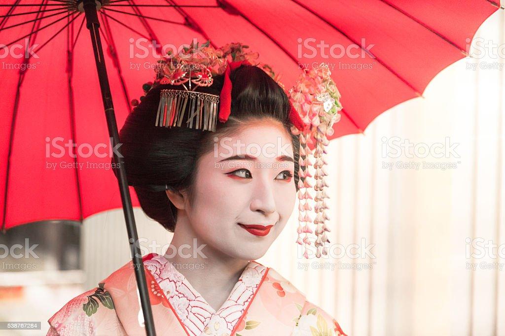 Smiley geisha walking with red umbrella in historic Kyoto stock photo