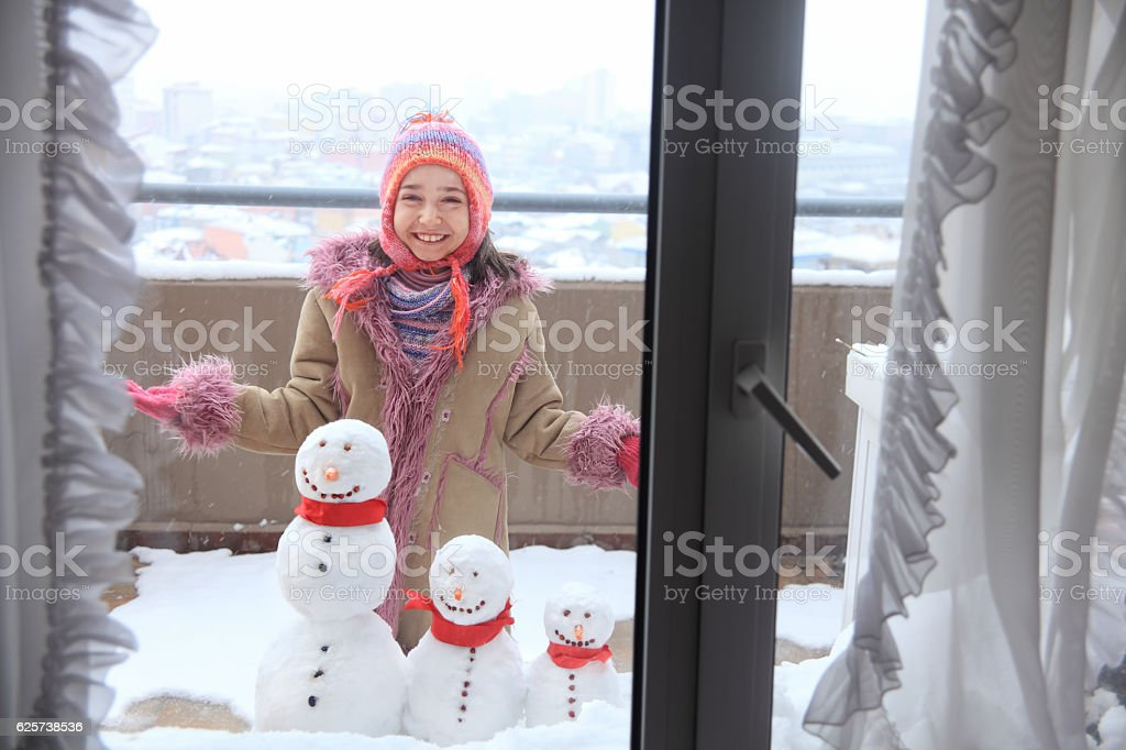 smiley girl and snowman family stock photo