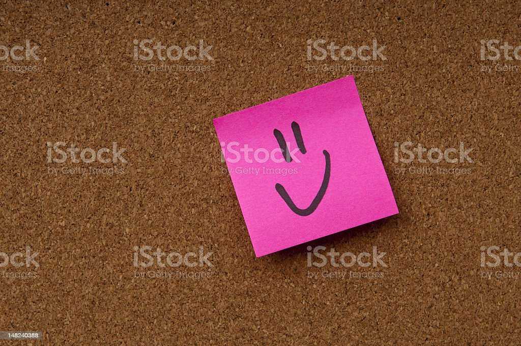 Smiley note on cork board stock photo