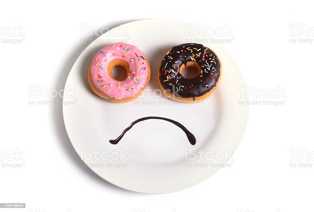 smiley sad face on dish with donuts eyes chocolate mouth stock photo
