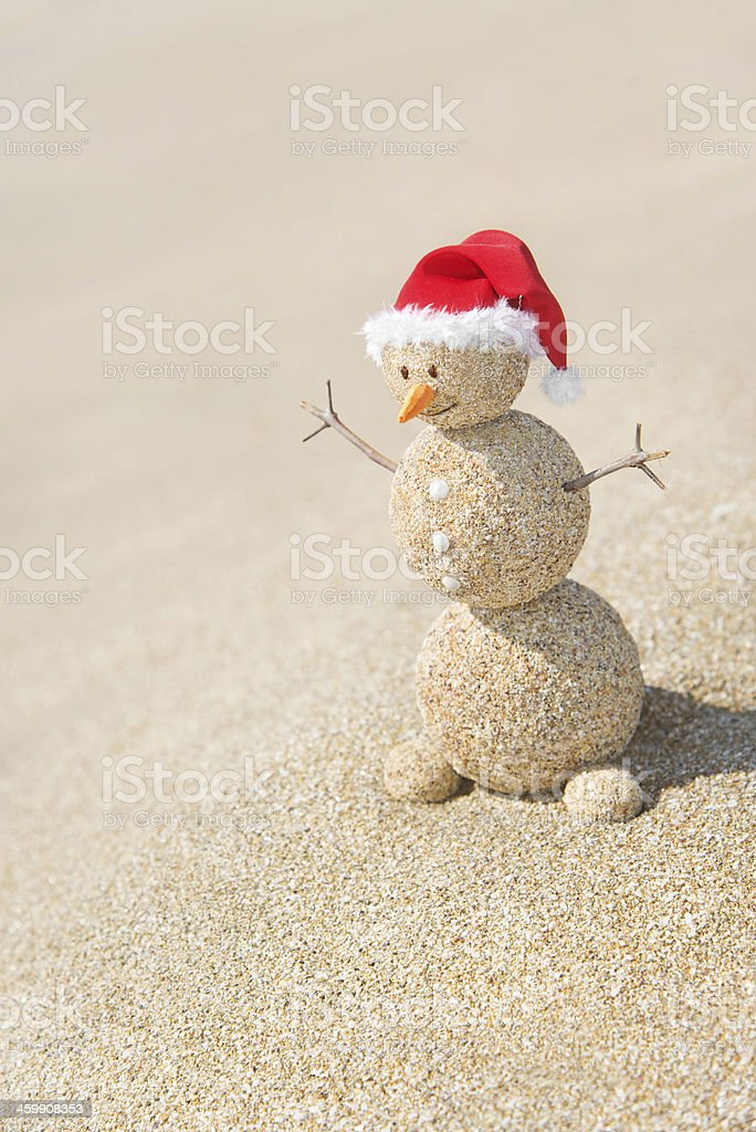 Smiley sandy snowman in santa hat. Holiday Christmas concept royalty-free stock photo