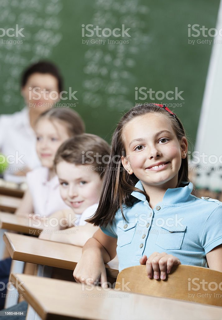 Smiley schoolgirl sits at the desk royalty-free stock photo