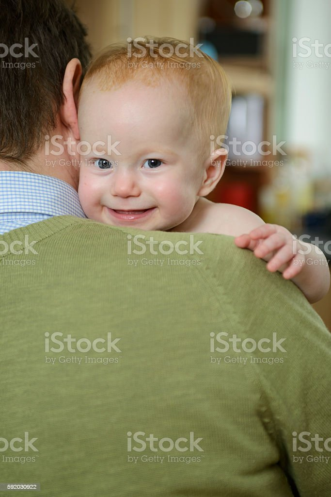 Smiley toddler - safe on daddy's shoulder stock photo