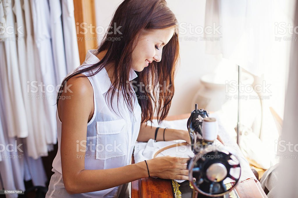 Smiley woman embroidering a white dress stock photo