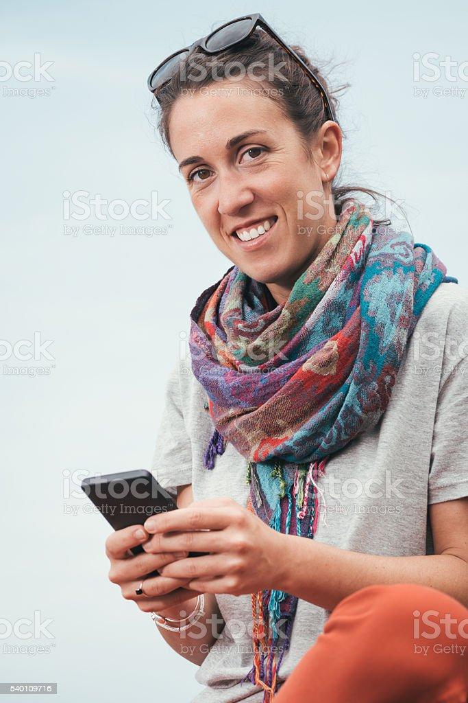 smiley woman sitting, texting on phone with sunglasses on summer stock photo