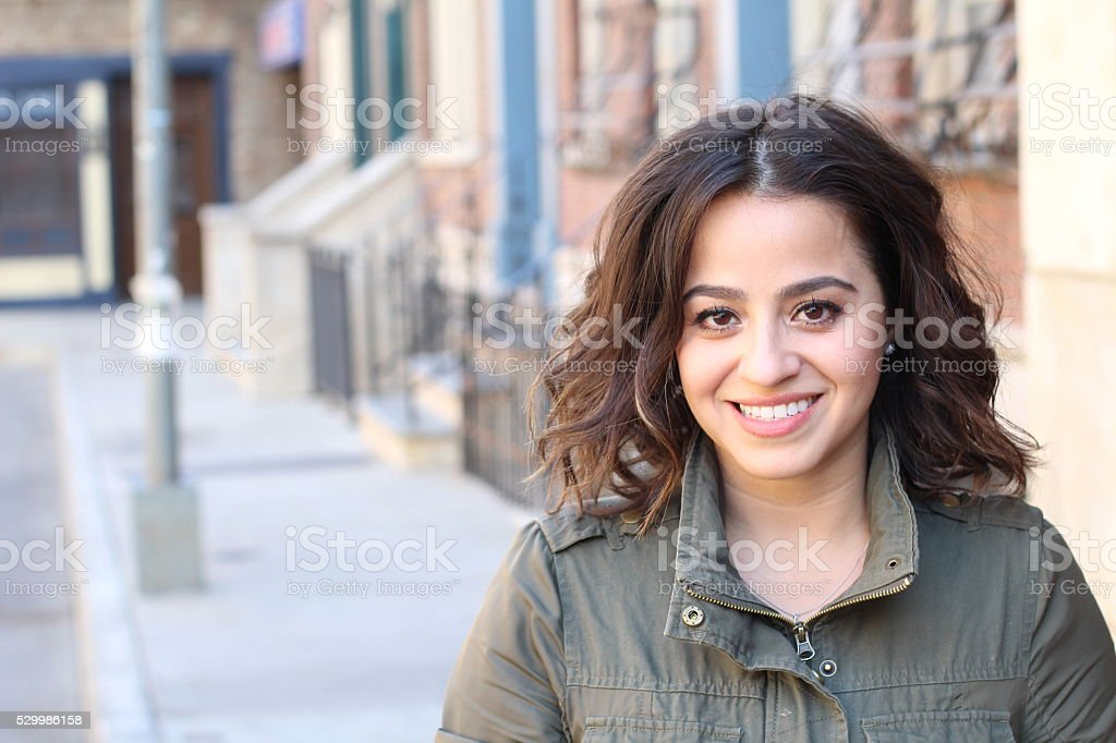 Smilie young woman in green jacket stock photo