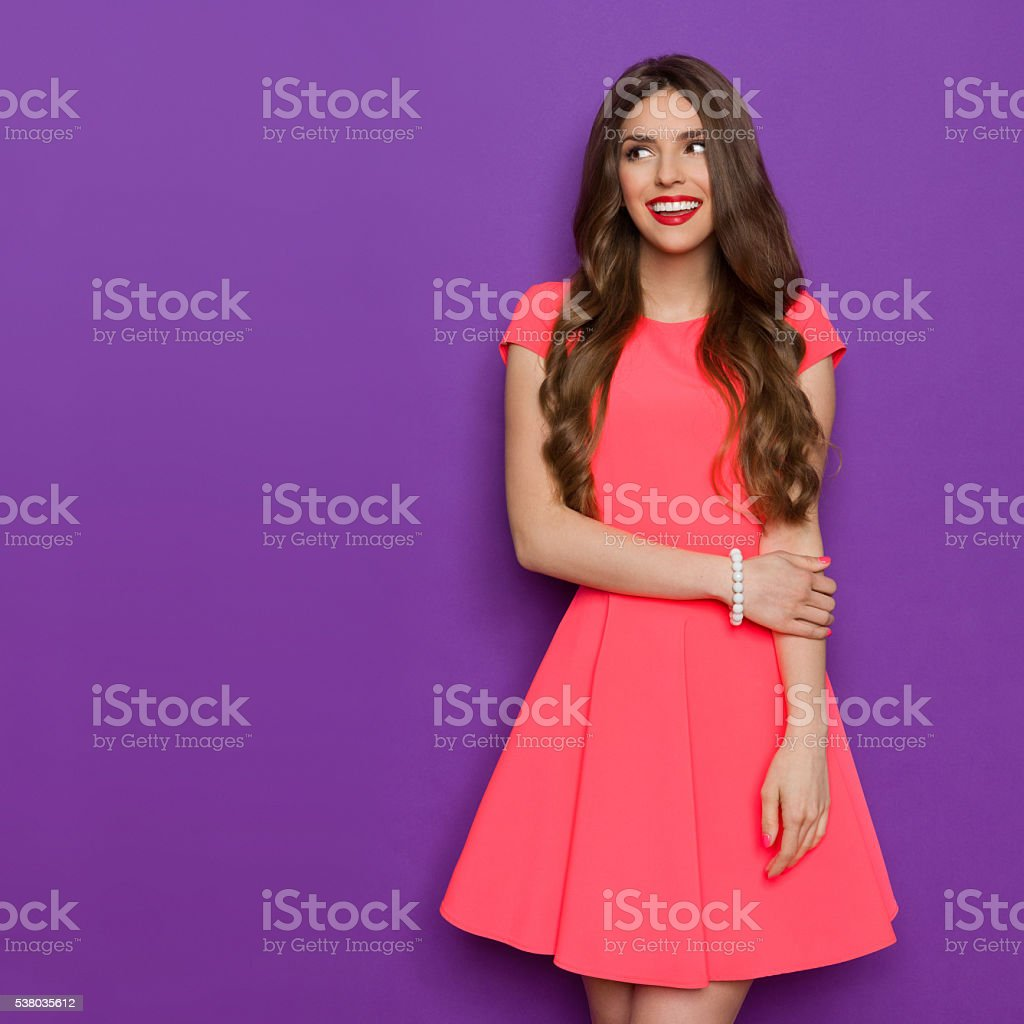 Smilin Girl In Pink Mini Dress Looking Away stock photo