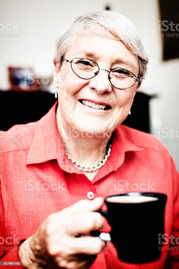 Smiling 70-plus woman holding coffee mug in her arthritic hand stock photo