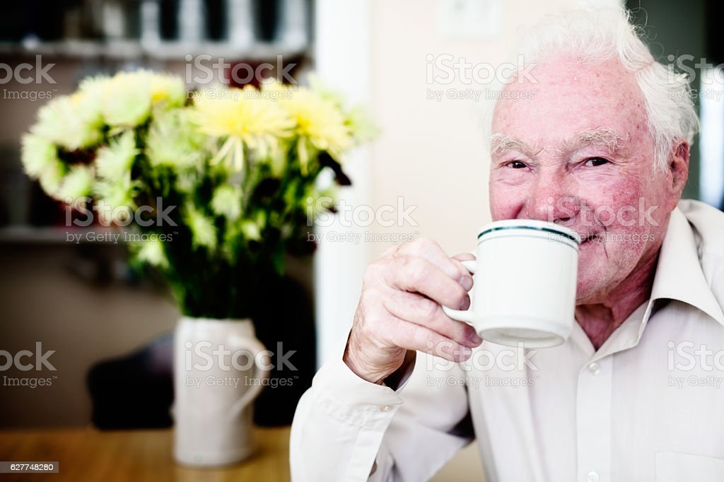 Smiling 80-plus old man enjoying cup of coffee stock photo