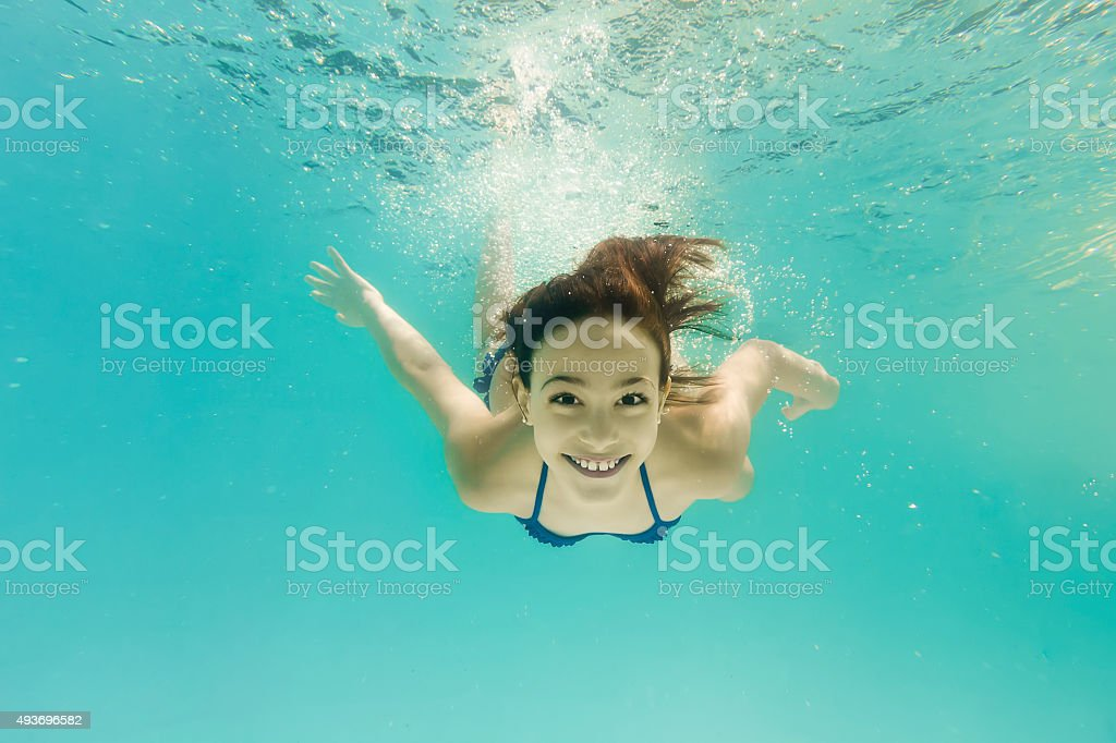 Smiling 8-Year-Old Girl Diving Underwater stock photo