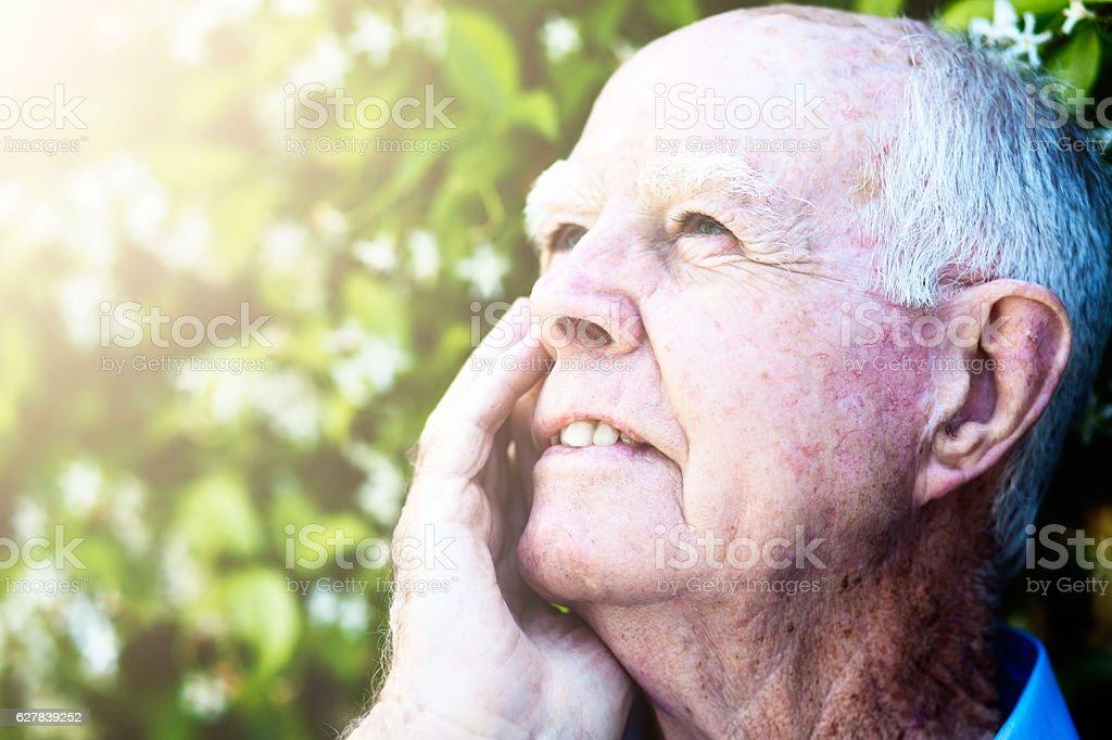Smiling 90-year-old man enjoying the sunshine in his garden stock photo