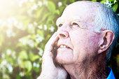 Smiling 90-year-old man enjoying the sunshine in his garden