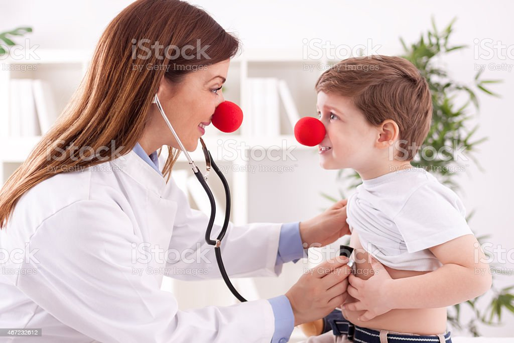 Smiling adorable female doctor clown listen patient heart stock photo