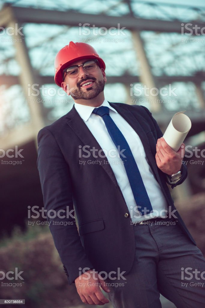 Smiling Adult Businessman With Blueprints and Construction Hat stock photo