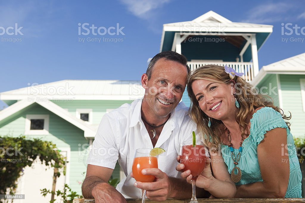 Smiling adult couple holding drinks royalty-free stock photo