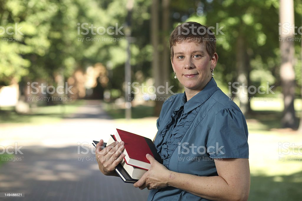 Smiling adult female student on campus smiles at the camera. stock photo
