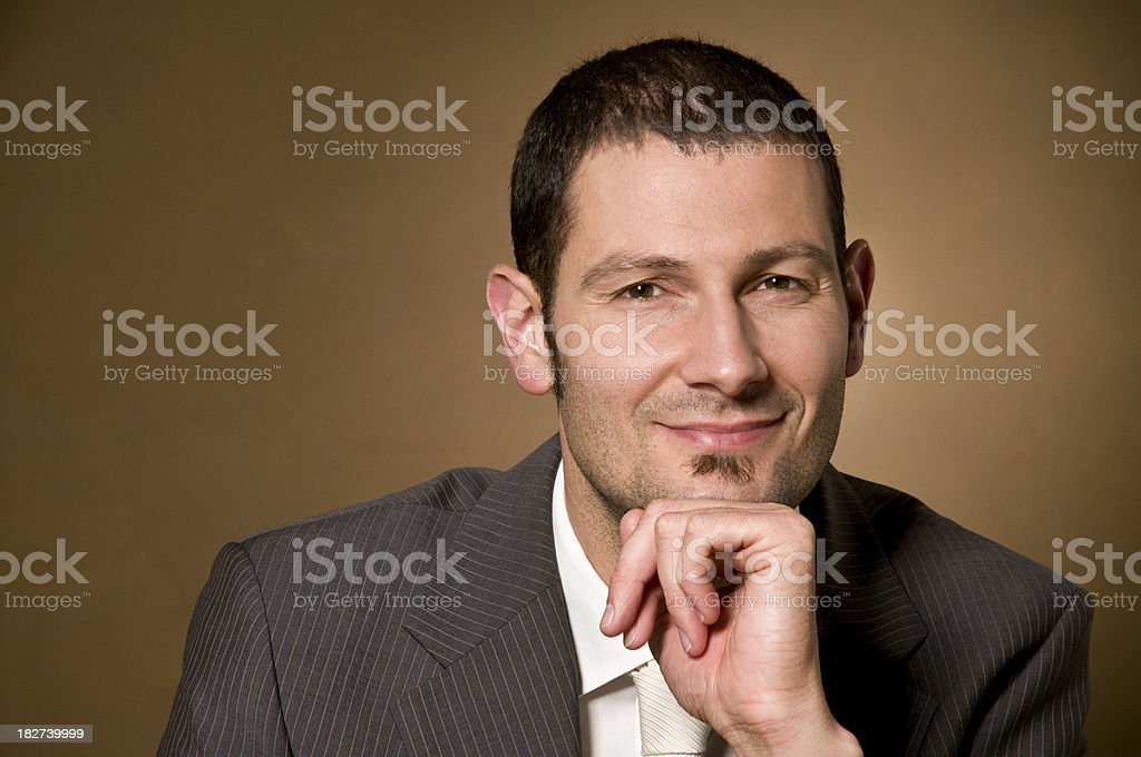 Smiling adult male leaning on his hand. royalty-free stock photo