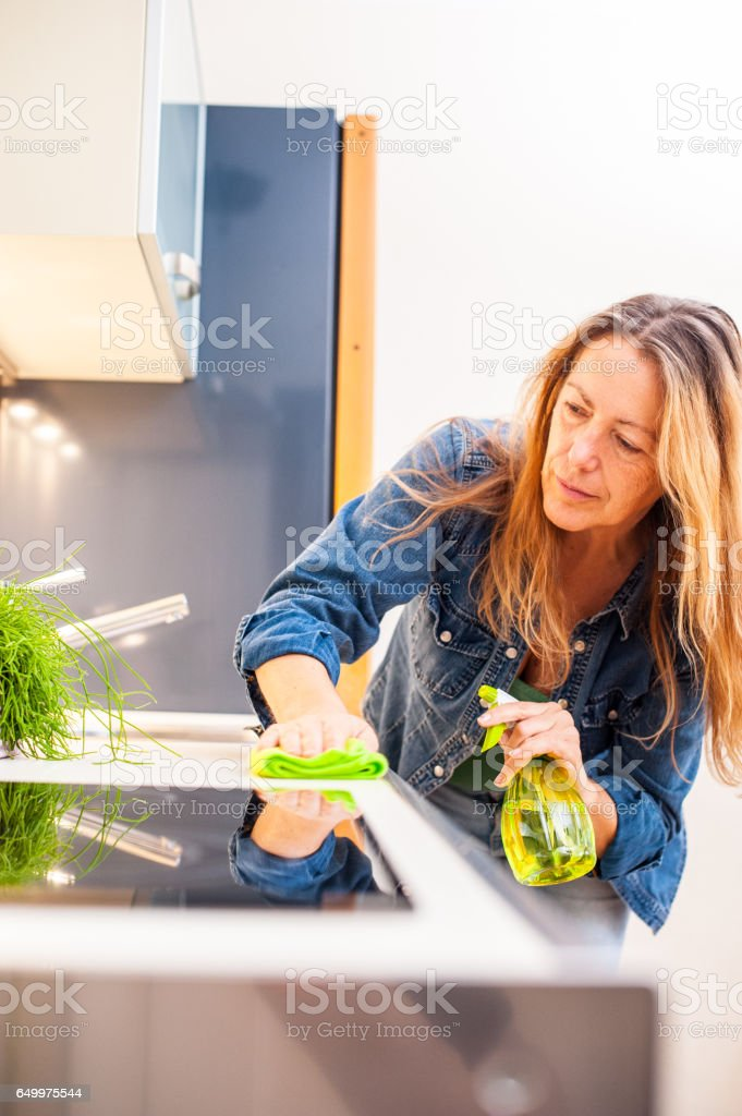 Smiling Adult Woman Cleaning Kitchen stock photo