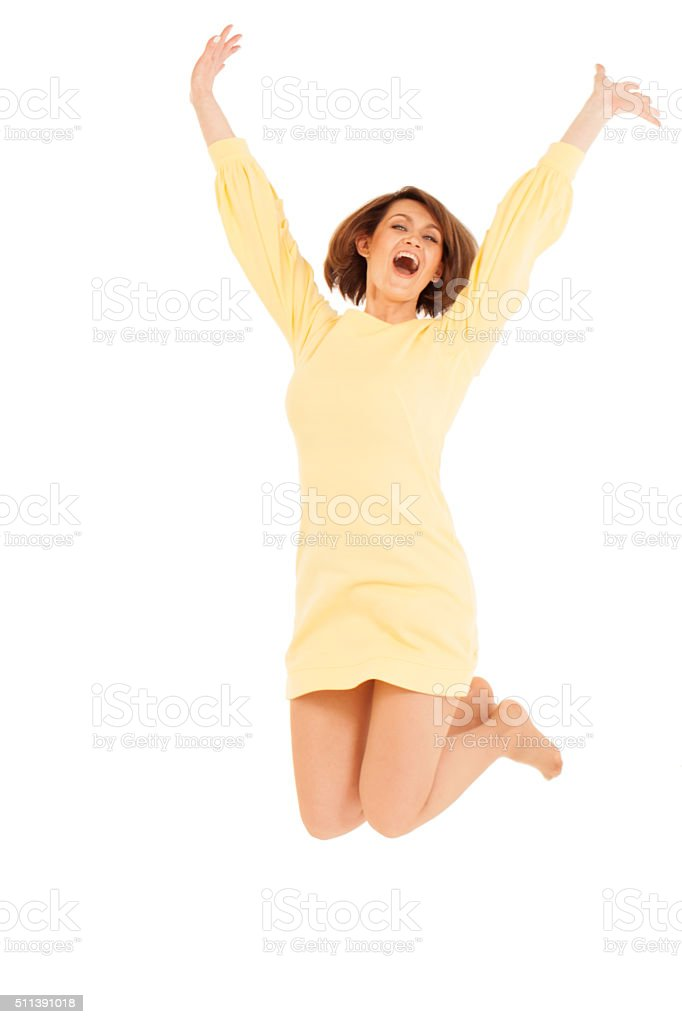 Smiling adult woman jumping with hands up stock photo