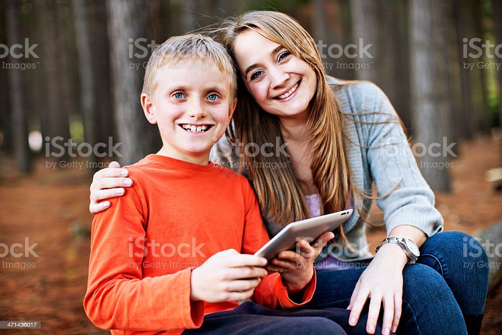 Smiling affectionate mother and son with tablet pc stock photo