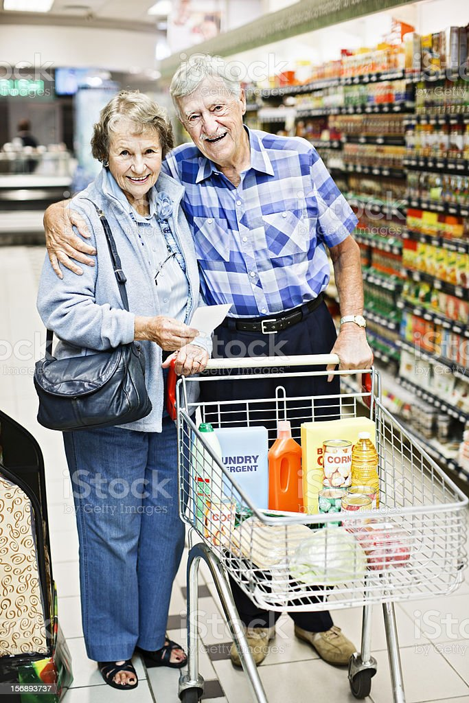 Smiling, affectionate senior couple in supermarket stock photo