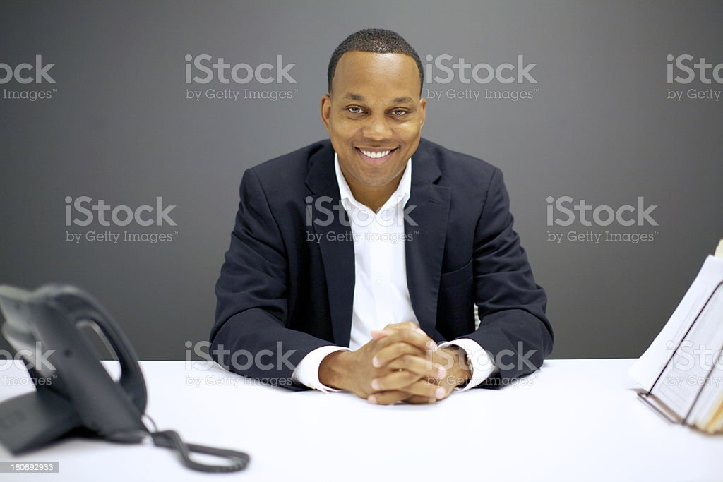 Smiling african american businessman at desk stock photo