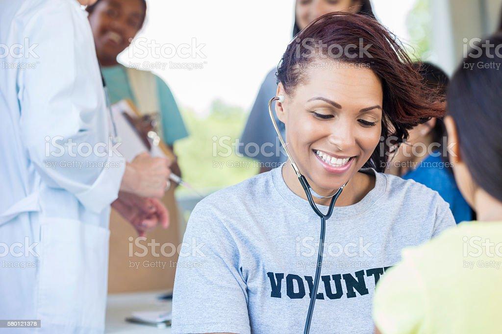 Smiling African American Nurse in volunteer shirt stock photo