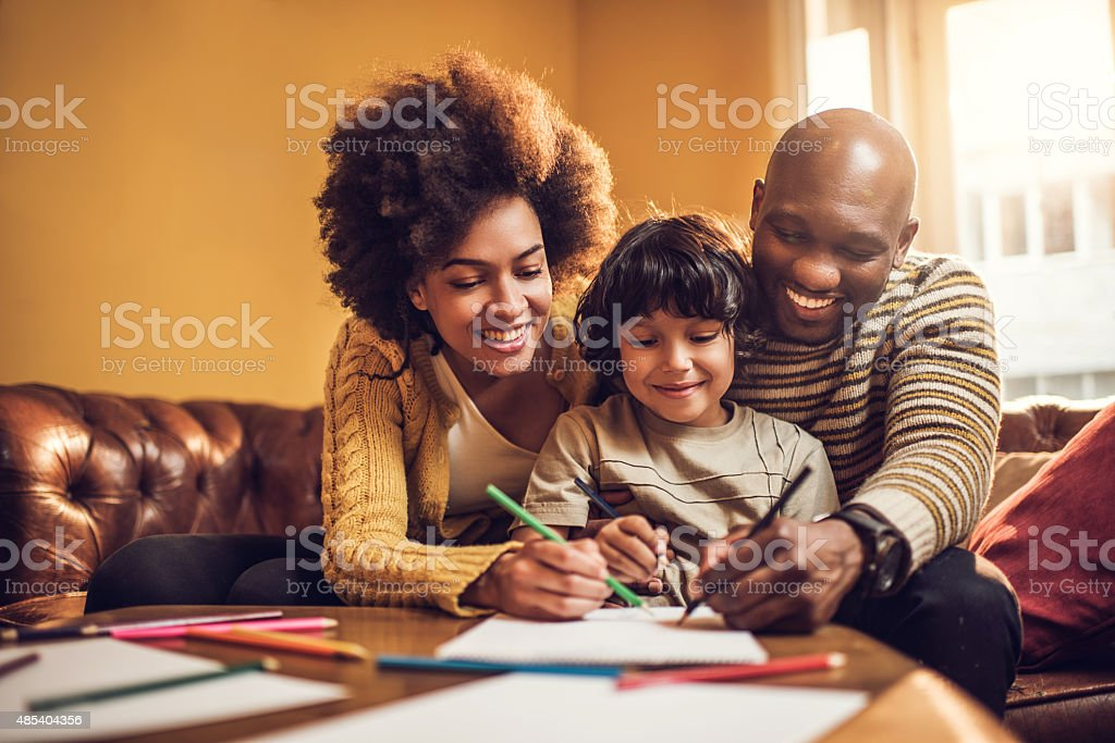 Smiling African American parents coloring with their little boy. stock photo