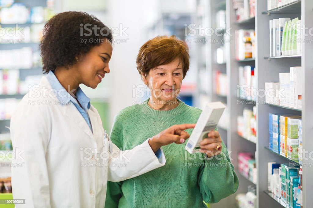 Smiling African American pharmacist assisting senior customer in a pharmacy. stock photo