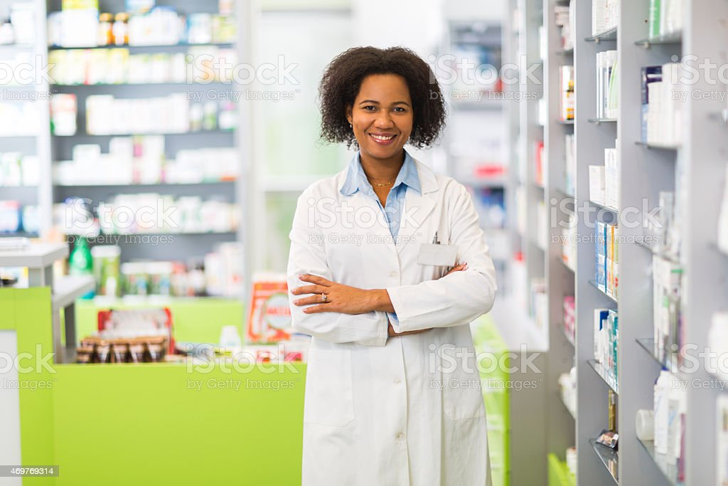 Smiling African American pharmacist standing in pharmacy. stock photo