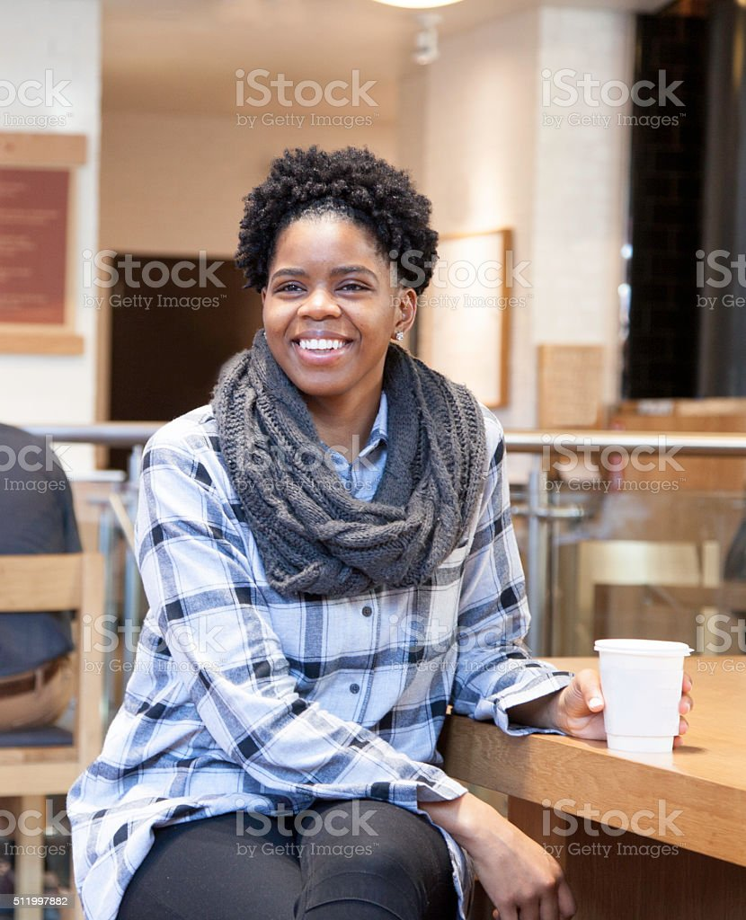 Smiling African American Woman sitting in Coffee Shop stock photo