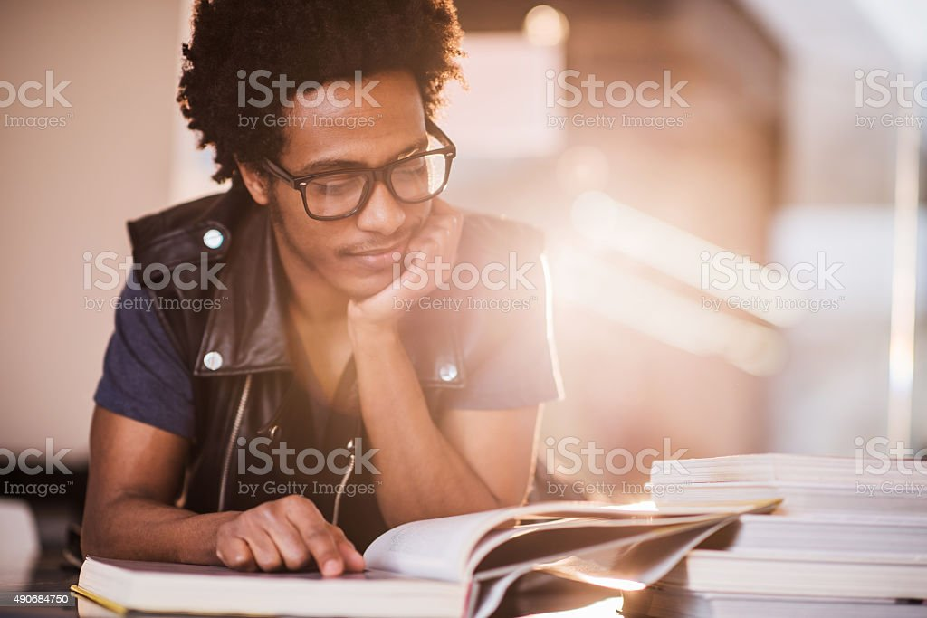 Smiling African American young man studying. stock photo