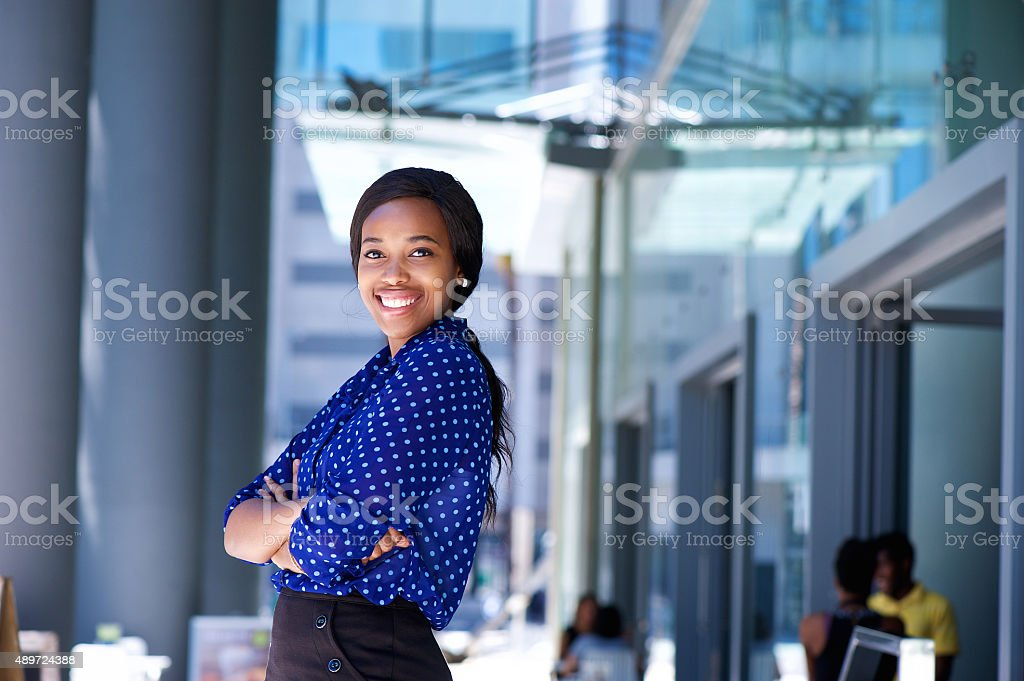 Smiling african business woman with arms crossed stock photo