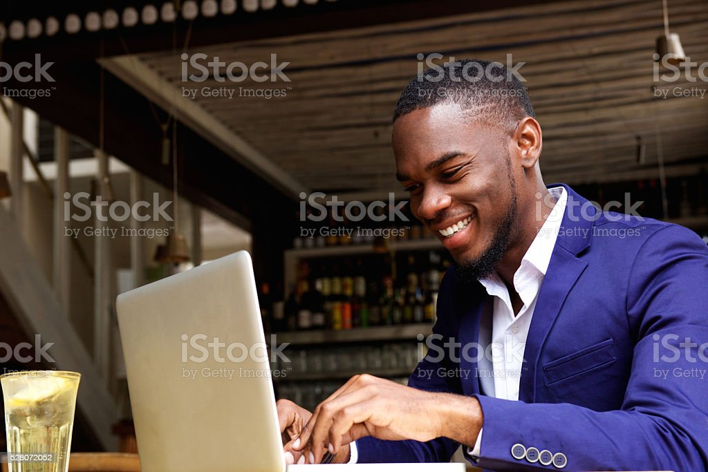 Smiling african businessman working on laptop at cafe stock photo
