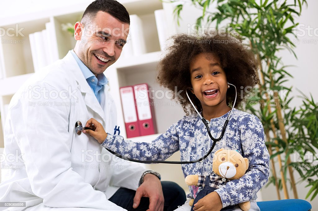 Smiling african girl playing with pediatrician stock photo