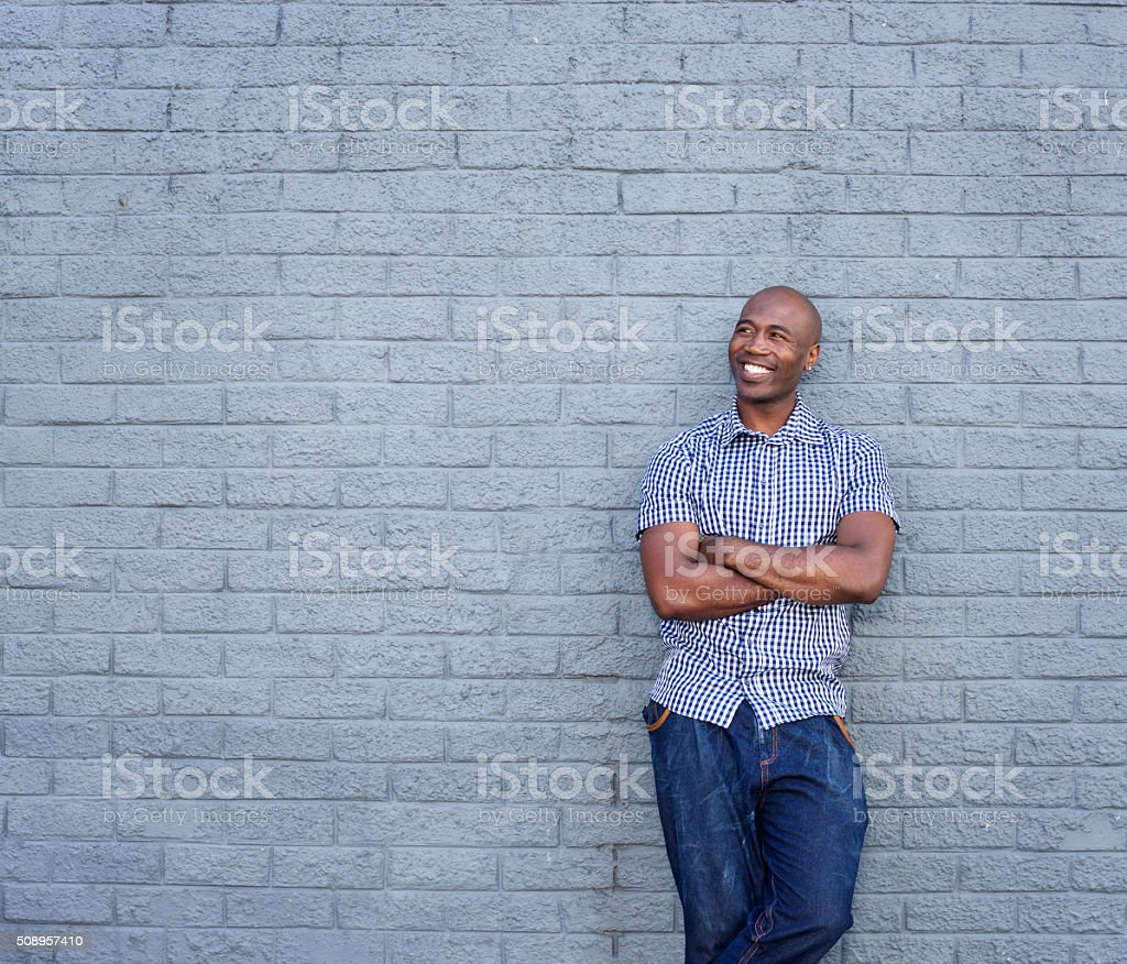 Smiling african man standing with his arms crossed stock photo
