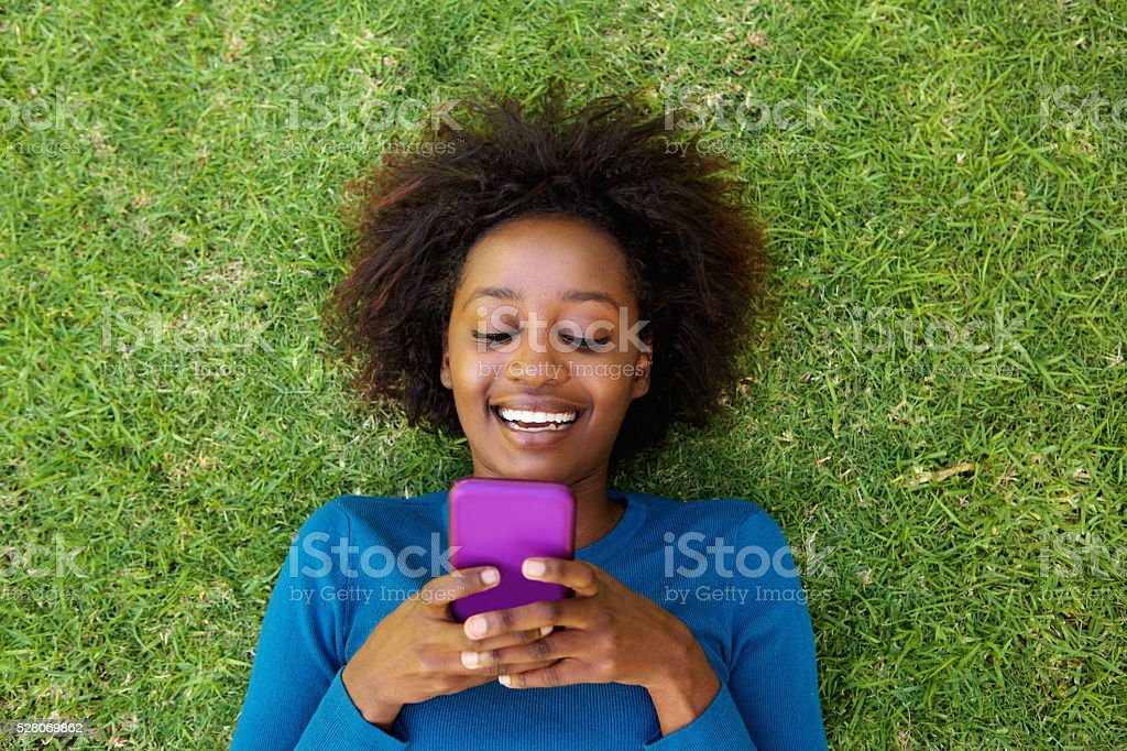 Smiling african woman lying on grass looking at cell phone stock photo