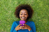 Smiling african woman lying on grass looking at cell phone