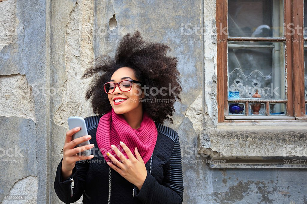 Smiling african woman making selfie in front of vintage building stock photo