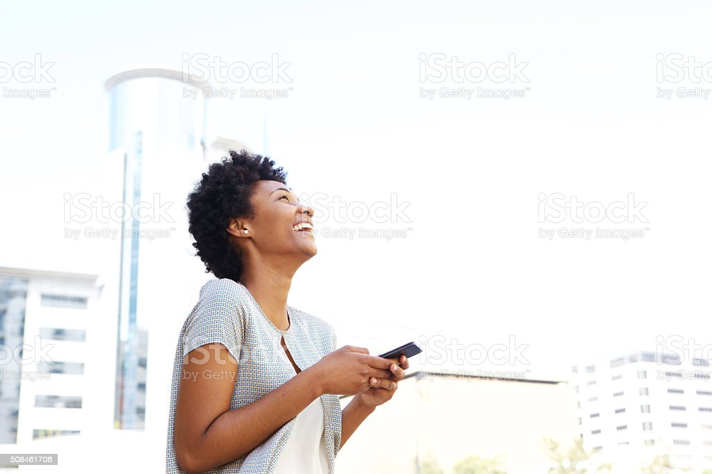 Smiling african woman standing outside holding cell phone stock photo