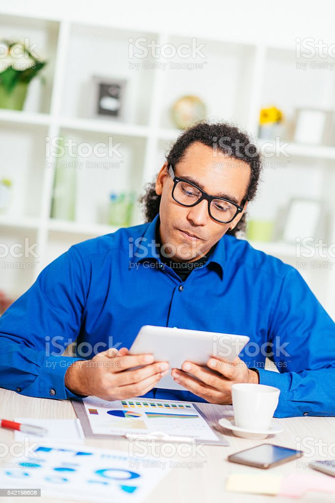 Smiling African-American businessman reading news on digital tablet stock photo