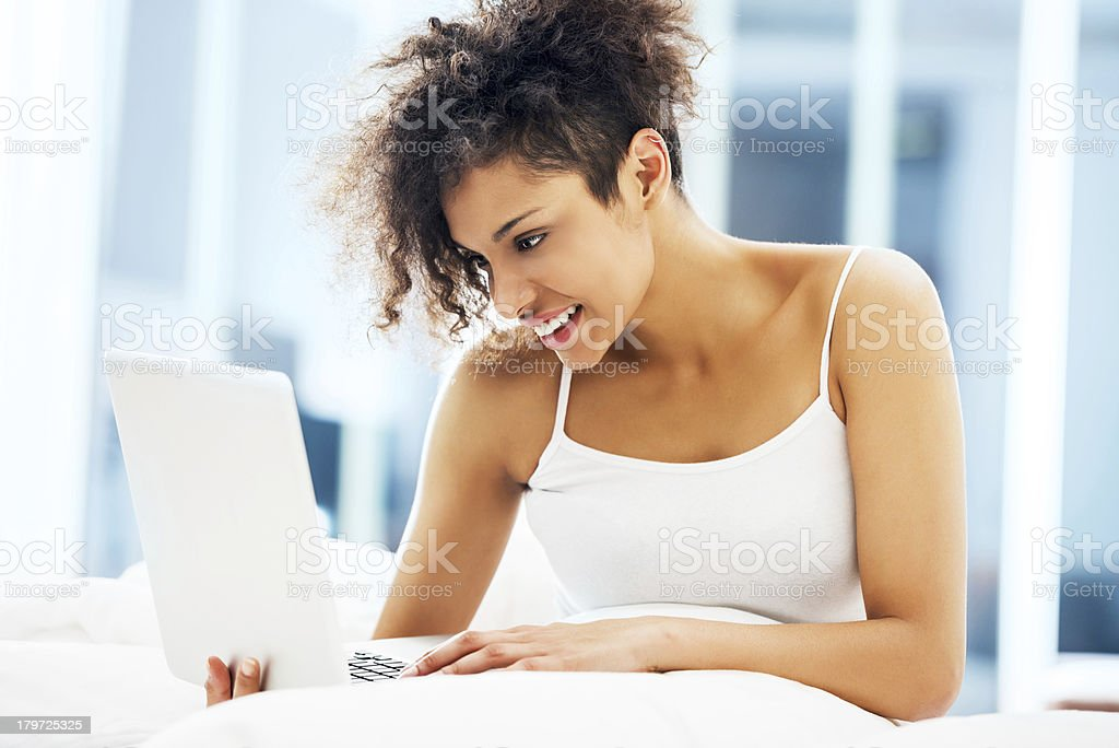 Smiling African-American woman using laptop in bed. royalty-free stock photo