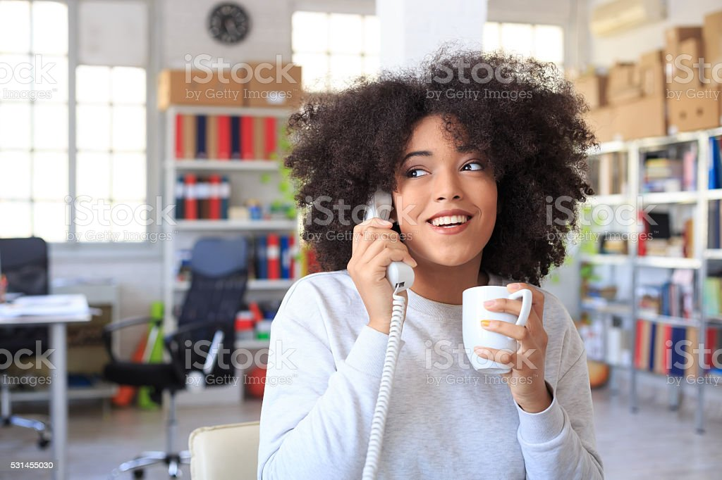 Smiling afro bussinesswoman drinking coffee and talking on phone stock photo