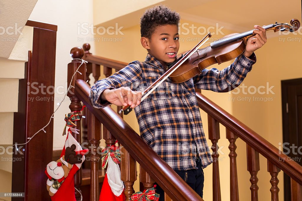Smiling afro kid plays violin. stock photo