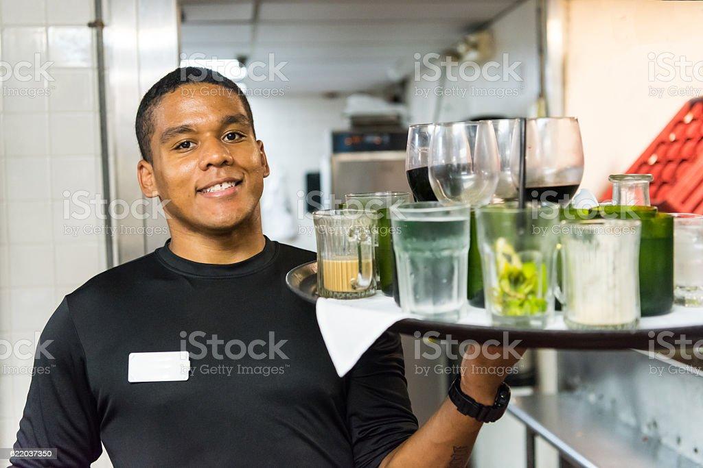 Smiling afro-caribbean waiter busboy stock photo