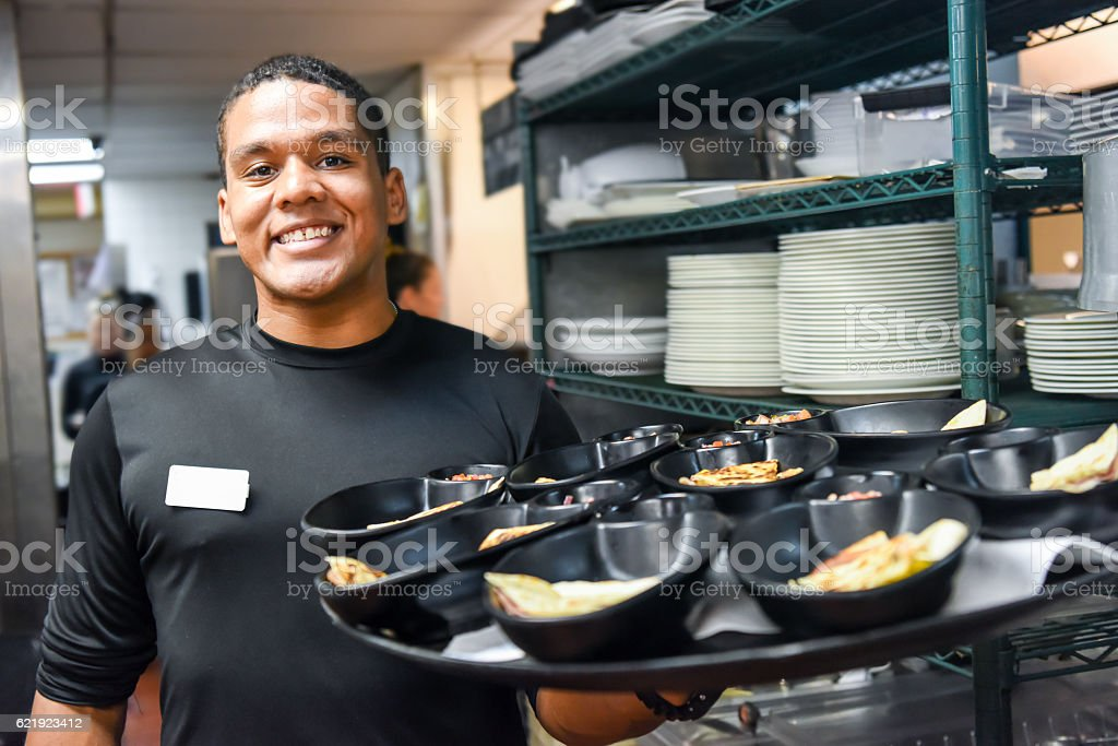 Smiling afro-caribbean waiter stock photo