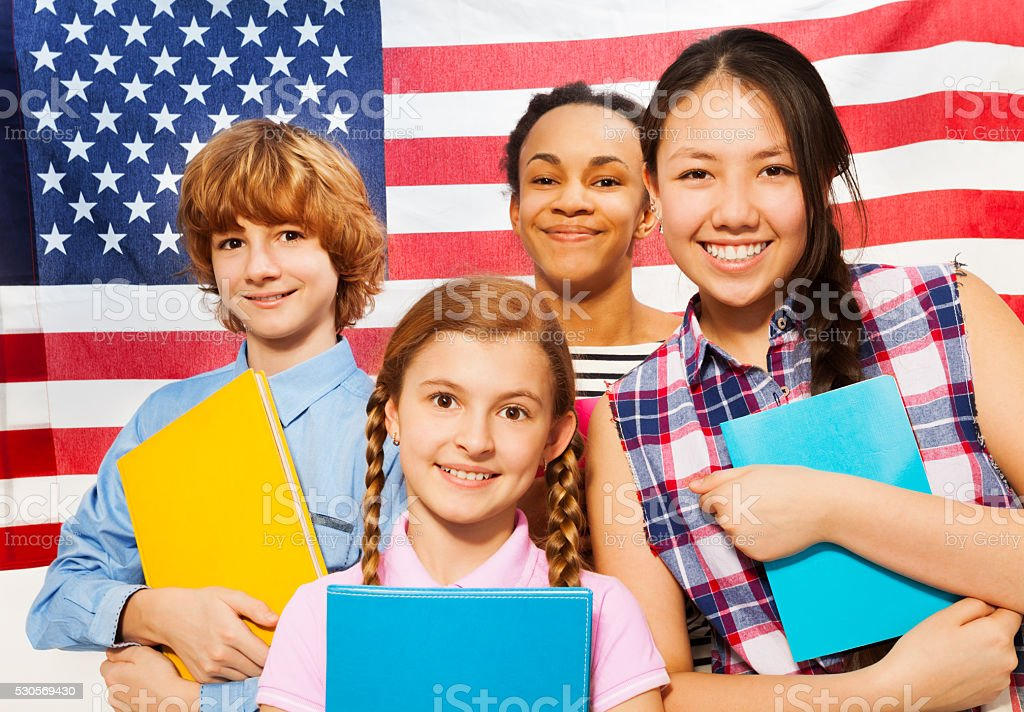 Smiling American teenage students with textbooks stock photo